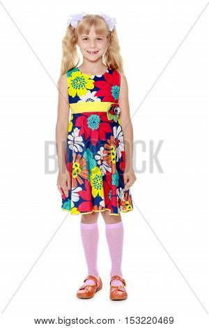 Beautiful little girl with long blonde ponytails on her head tied with white bows, bright summer dress and knee socks