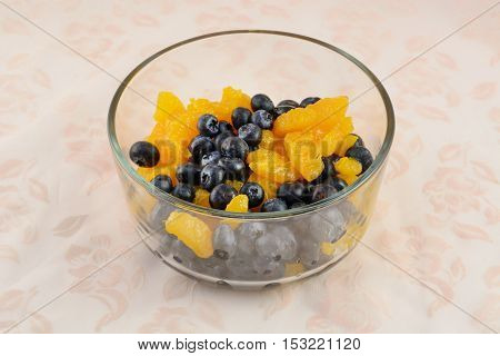 Simple fruit salad of fresh blueberries and canned mandarin oranges in glass bowl