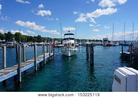 HARBOR SPRINGS, MICHIGAN / UNITED STATES - AUGUST 3, 2016: A yacht enters a slip at the Harbor Springs Municipal Marina.
