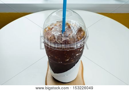 Cold coffee in plastic cup on wooden table in cafe. Cup of espresso coffee.