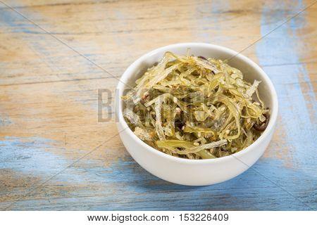 a small ceramic bowl of seaweed salad based on agar-agar against grunge wood