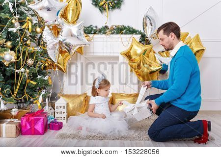 Father and daughter unpack gifts at the Christmas tree. The father gives his daughter a gift and a cute little girl sitting on the floor. The festive mood. Family celebration.