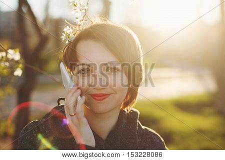 Cute girl talking on a cell phone against the backdrop of the setting sun. Close-up portrait. The solar lens flare.