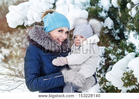 Mother and young daughter embracing in a winter park. A happy family. Childhood and parenthood happiness. Close portrait.
