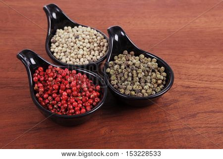 fresh dry peppercorn in small black bowl on wooden table ready to cook