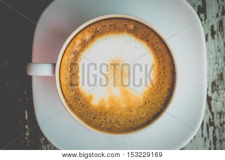 A Cup of hot latte art coffee on wooden table.