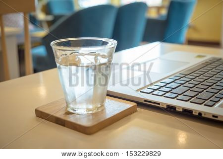 Laptop computer on wood table with glass of water cold. (focus on laptop)