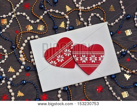 New Year's card with a beads confetti an envelope and red decorative elements in the form of heart. Christmas background. The letter for Santa.