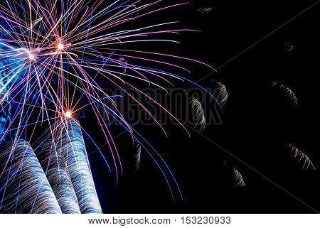 Colorful holiday fireworks on black sky background
