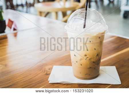 Cold coffee in plastic cup on brown wooden table at cafe. (soft focus)