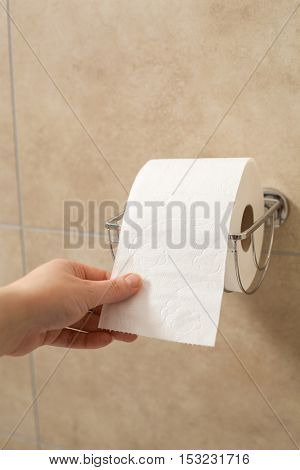 hand holding toilet paper roll in holder