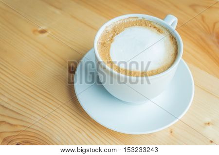 Cup of coffee and saucer on wooden table in cafe.