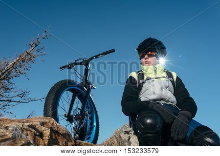 Fatbike also called fat bike or fat-tire bike - Cycling on large wheels. Traveller cyclist sits on top of the mountain. He is resting on a trip looking at the sunset.