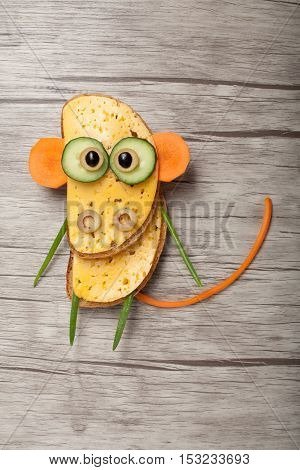 Monkey made of bread and vegetables on wooden background