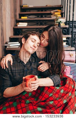 Dreaming on wooden stairs couple, free space. Young man with woman having snap while decorating home before Christmas holidays. Love, tire, calm concept
