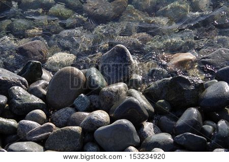 Wet stones on the seashore partly covered by the clear sparkling sea.