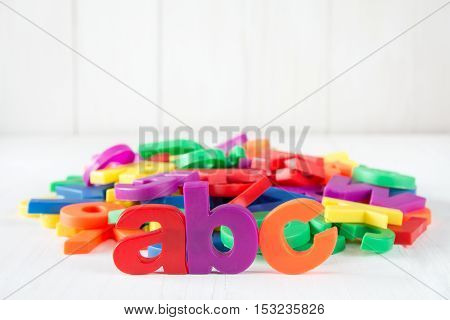ABC spelling and pile of colorful plastic letters on white wooden background