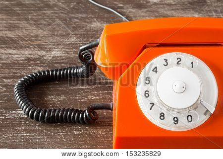 Close up view of part of old orange telephone