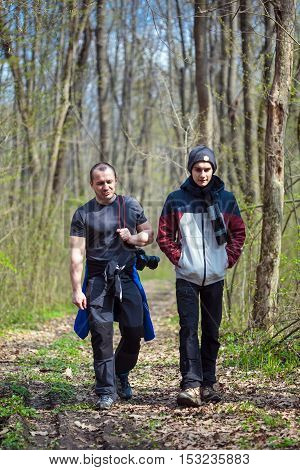 Father and teenage son having a walk in the forest
