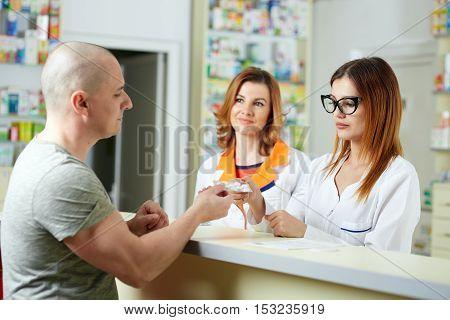 Pharmacists giving a customer medicine