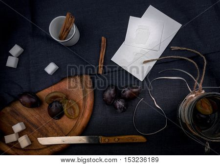 Sweet homemade plum jam and fruits on a wooden table.