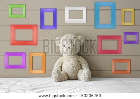teddy bear sit on the white bed with blank multi-color or fancy picture frame at the headboard and brown wall background for gift and surprise