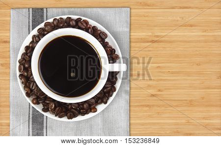 top view dark coffee with beans in white cup on plate mat and wood table with space for your text or object