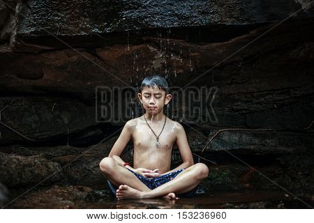 Boy meditating under a waterfall rocks in the woods somewhere.