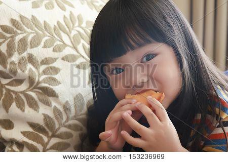 asian child or little girl enjoy eating a custard cake in the room