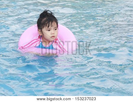 Children or baby girl play in the swimming pool or water park with hugging pink life ring