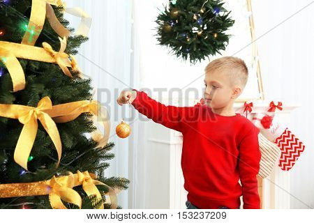 Cute little boy decorating Christmas tree at home
