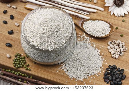 white sesame black bean white bean and mung bean in glass cup with spoon and on the wood table for diet and healthy food background