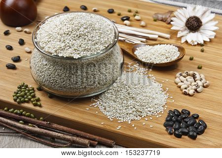 white sesame white bean black bean and mung bean in glass cup with spoon and on the wood table for diet and healthy food background
