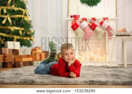 Cute little boy lying on carpet at home