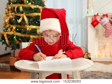 Cute little boy writing letter to Santa Claus at table