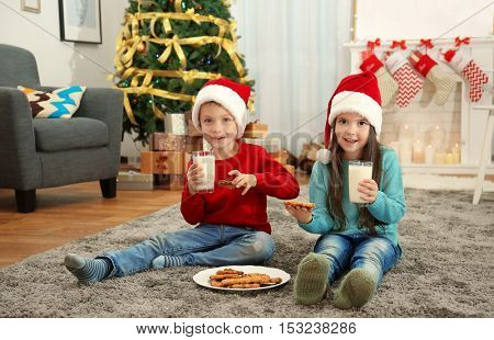 Cute little kids in Santa hats drinking milk and eating delicious cookies at home