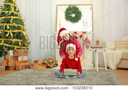 Cute little kids in Santa hats with Christmas present at home