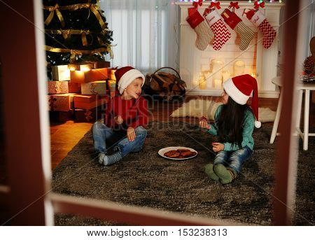 Cute little kids in Santa hats eating delicious cookies at home, view through window