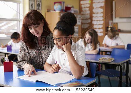Primary school teacher helping a schoolgirl at her desk