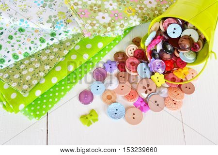 Pieces of cloth in flower and polka dot patterns. Little green pail with decorative colorful buttons. Buttons scattered on the table. Fabric and buttons set. Sewing concept
