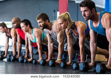 People doing push-ups with dumbbell while exercising in gym