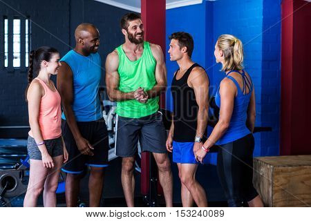 Smiling friends discussing while standing in gym