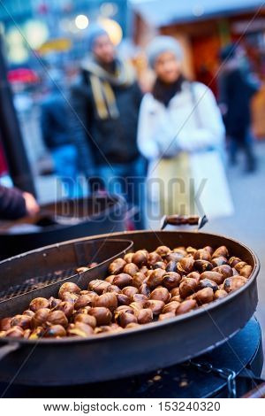 Closeup photo of roasted chestnuts at wintertime on the street.