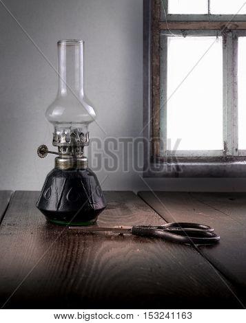 kerosene lamp and scissors on a background window