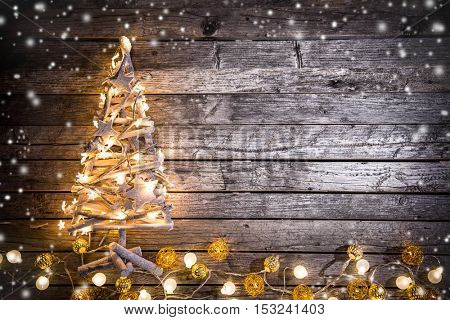 Abstract christmas background with shiny crafted tree and little lights.