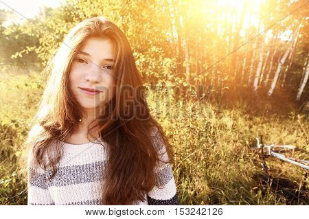 Beautiful smiling teen girl with long brown hair portrait with bike in a country field
