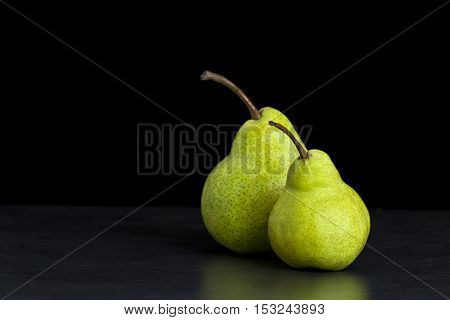 Two fresh tasty green pears next to each other isolated on a black background facing left