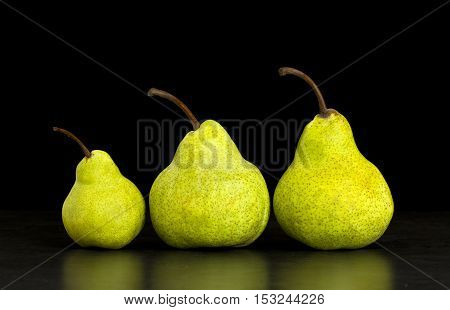 three pears standing in a straight row on a black isolated background