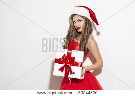 Charming brunette woman in red sants claus outfit holding big xmas present isolated on the white background