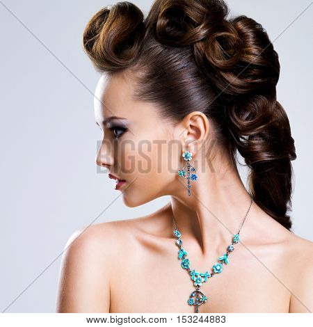 Profile portrait of a beautiful young woman with creative hairstyle  and bright colored eye makeup. Fashion model wear blue earring and necklace